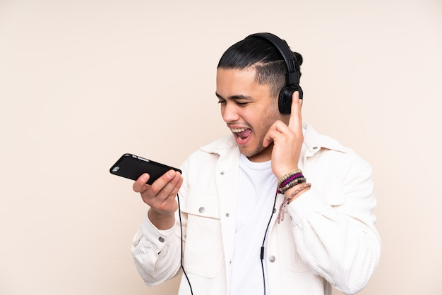 Asiatischer schöner mann lokalisiert auf beige wand, die musik mit einem handy und gesang hört