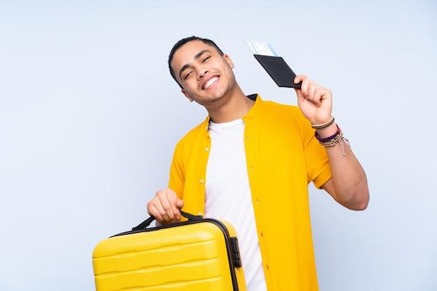 Asiatischer schöner mann lokalisiert auf blauem hintergrund im urlaub mit koffer und pass