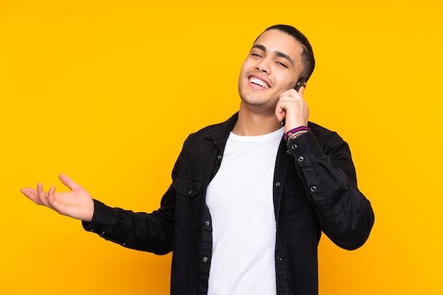 Asiatischer schöner mann lokalisiert auf gelber wand, die mund mit händen bedeckt