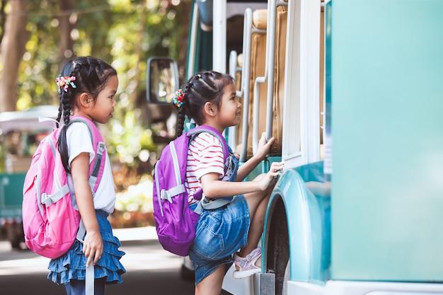 Asiatischer schüler scherzt mit dem rucksack, der hand hält und zusammen mit schulbus zur schule geht