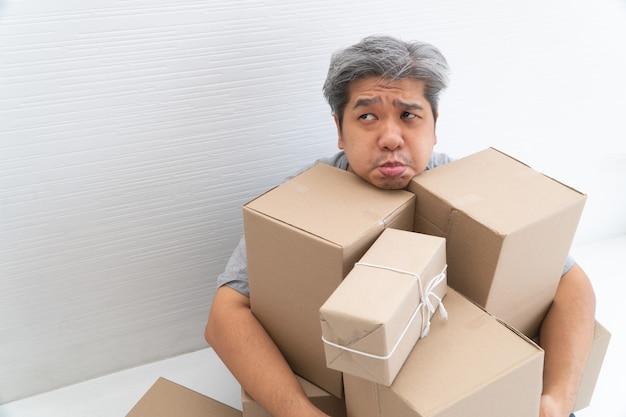 Asiatischer shopaholic sitzt auf dem boden im wohnzimmer