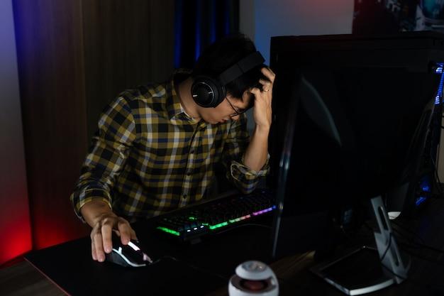 Asiatischer spieler in kopfhörern, die mit der hand gestresst sind, fühlen sich deprimiert oder wütend geschockt, wenn sie das videospiel auf dem computer verlieren. angst und verärgerung über fehler, videospieltechnologie und e-sport-konzept