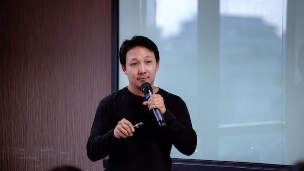 Asiatischer sprecher der nahaufnahme oder vortrag mit zufälliger klage auf dem stadium vor dem raum presen
