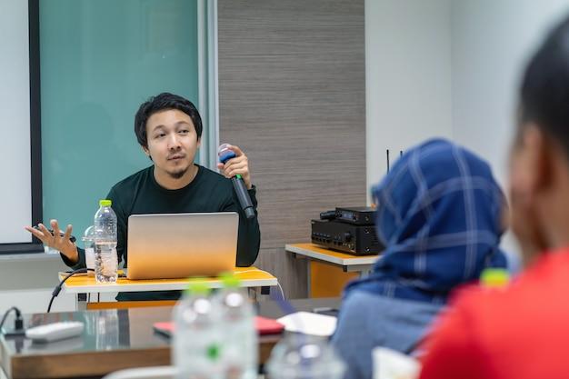 Asiatischer sprecher oder vortrag mit dem zufälligen anzug, der rede vor dem raumdarstellen gibt