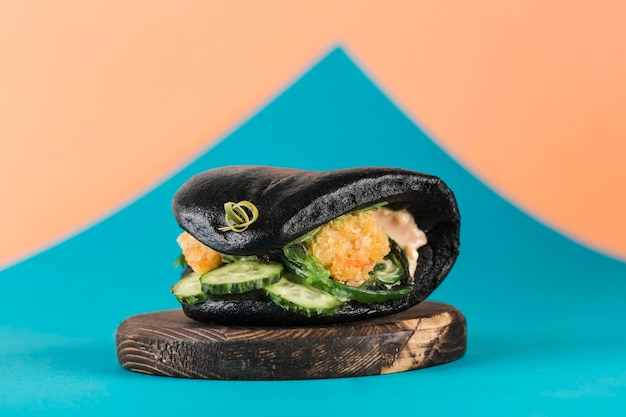 Asiatischer straßen-fast-food-bao-burger mit panierten garnelen, frischen gurken und seetang in einem schwarzen tintenfisch