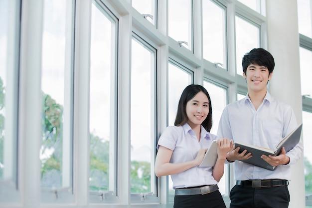Asiatischer student, der eine tablettenlesung hält