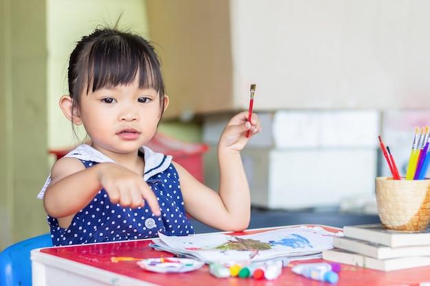 Asiatischer student, der farben auf dem papier im raum zeichnet und malt.