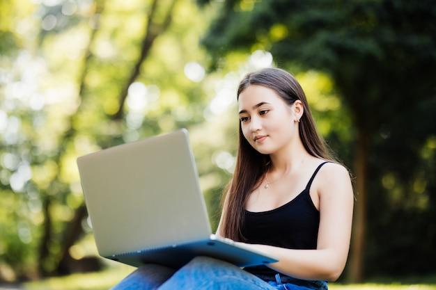 Asiatischer student, der mit grünem parkkonzept des computerlaptops im freien des universitätscampus arbeitet