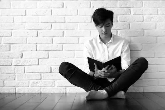 Asiatischer student des jungen mannes mit büchern in den händen