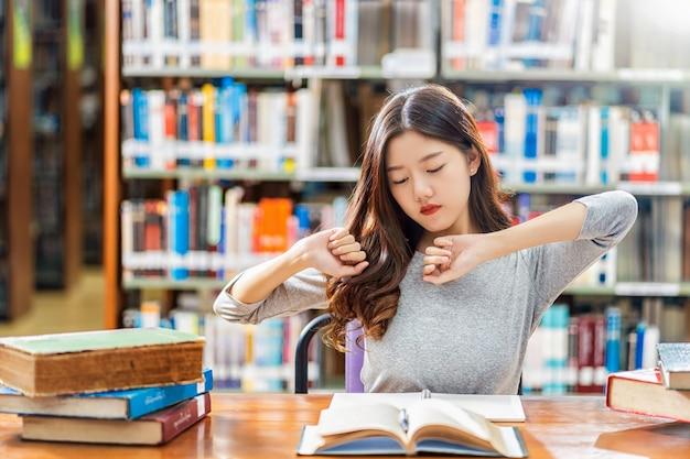 Asiatischer student in der zufälligen klage lesend und tuend dehnen sich in der bibliothek der universität aus