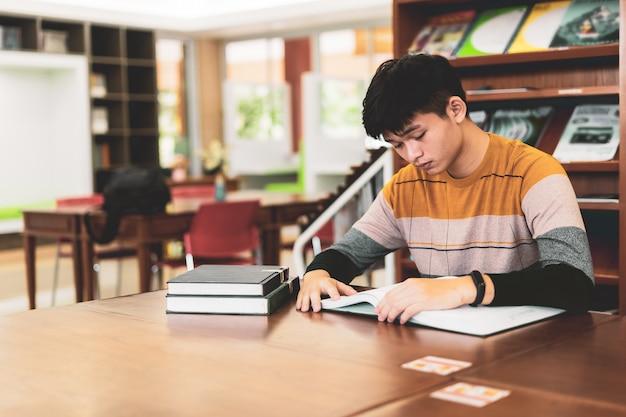 Asiatischer student liest buch in der bibliothek, lektionen für prüfungen, pädagogische konzepte