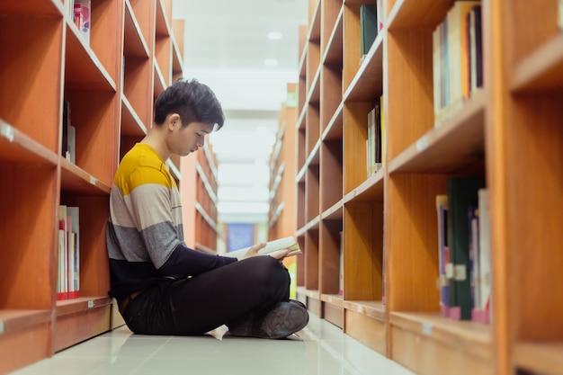 Asiatischer student liest buch in der bibliothek, unterricht für prüfungen, bildungskonzepte
