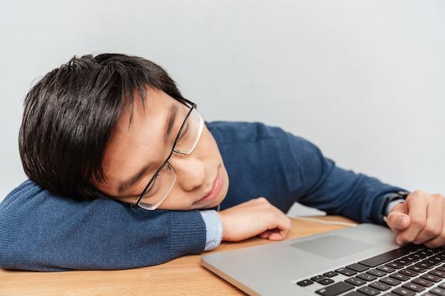 Asiatischer student schläft am tisch. mit laptop. nahansicht