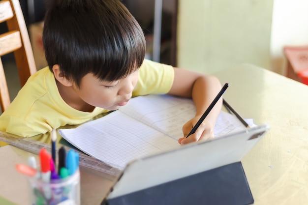 Asiatischer studentenjunge, der smart pad oder tablet für seine hausaufgaben verwendet und berührt