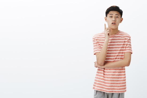 Asiatischer süßer kerl, der versuch macht, vorschlag hinzuzufügen oder frage zu stellen, während er interessante vorlesung besucht, zeigefinger offenen mund hebt und interessiert aussieht