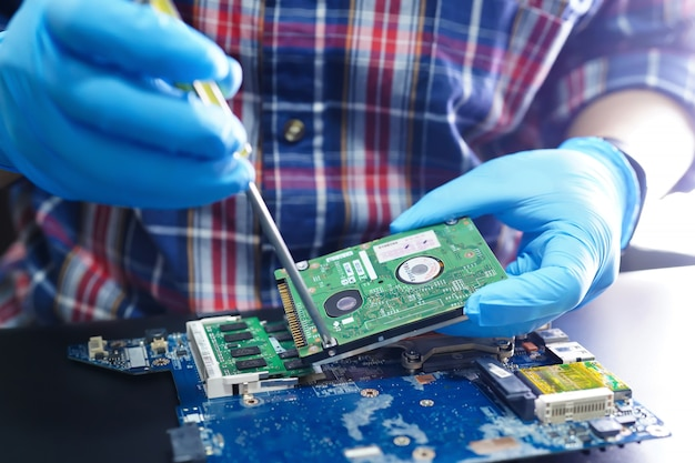 Asiatischer techniker, der elektronische technologie des mikroschaltungshauptplatinencomputers repariert.