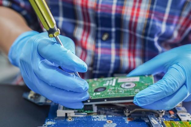 Asiatischer techniker, der hauptplatinencomputer der schaltung repariert.