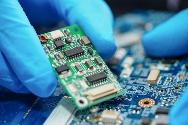 Asiatischer techniker, der mikroschaltungshauptbrettcomputer repariert.