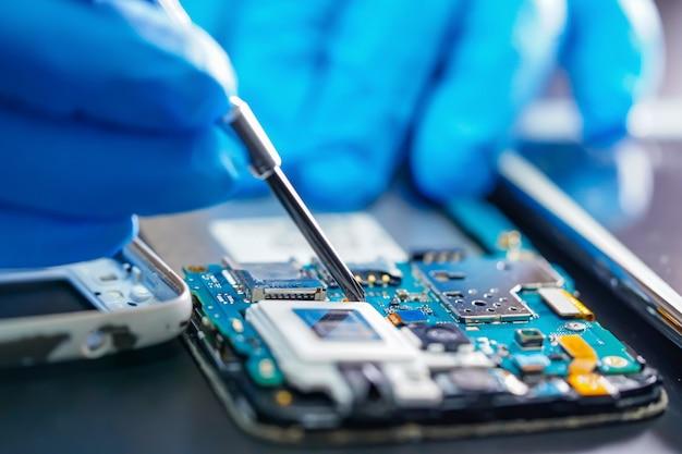 Asiatischer techniker, der mikroschaltungshauptplatine der elektronischen technologie des smartphone repariert.