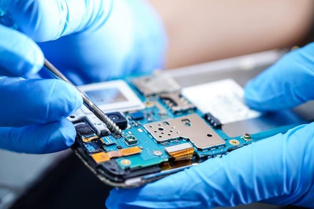 Asiatischer techniker, der mikroschaltungshauptplatine von smartphone repariert.