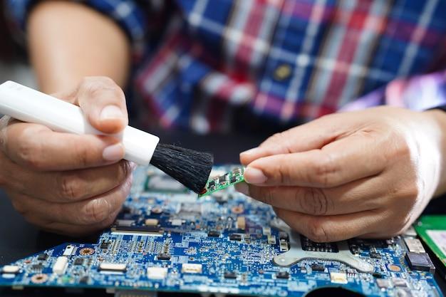 Asiatischer techniker, der schmutzigen staubmikroschaltungshauptbrettcomputer säubert.