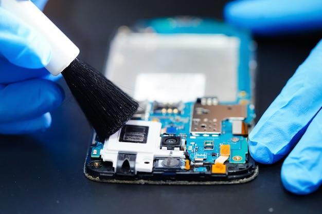 Asiatischer techniker reparieren und säubern schmutziges mikroschaltungshauptbrett von smartphone.
