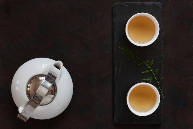 Asiatischer tee des weißen porzellans stellte mit grünem tee milch oolong auf schwarzem steinschreibtisch ein