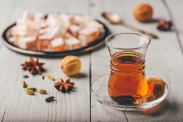 Asiatischer tee im armudu-glas mit rahat lokum und verschiedenen gewürzen über holzoberfläche