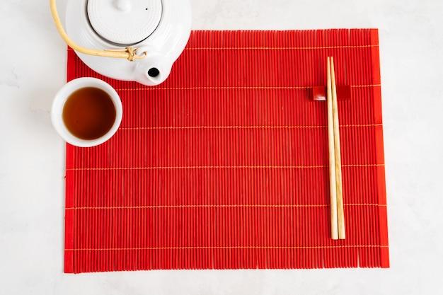 Asiatischer tee-nahrungsmittelhintergrund. teekanne und tasse mit stäbchen auf der roten bambusmatte über dem grauen steinhintergrund. modell für das menü.