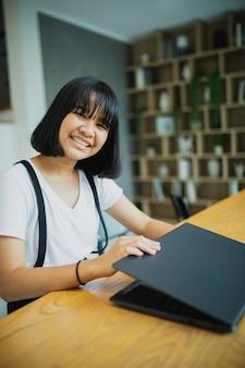 Asiatischer teenager, der an computer-laptop zu hause wohnzimmer arbeitet