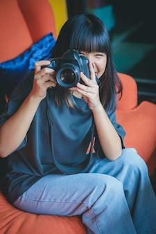Asiatischer teenager, der auf sofa sitzt und ein foto durch dslr-kamera macht