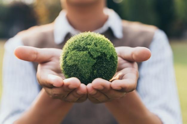 Asiatischer teenager, der das nachhaltige konzept der erde zur hand, der ökologie und der umwelt zeigt.
