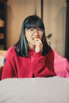 Asiatischer teenager, der sahnecracker zu hause esszimmer isst