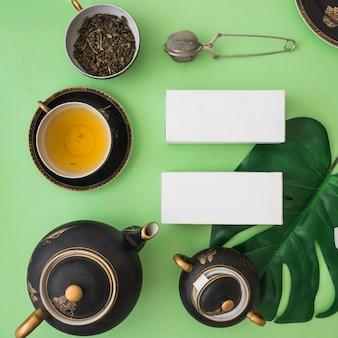 Asiatischer teesatz mit kräuterkästen auf grünem hintergrund