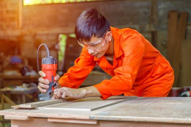 Asiatischer tischler des jungen mannes, der mit flugzeug auf hölzernem hintergrund arbeitet