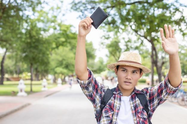 Asiatischer tourist, der den inhaber der schwarzen geldbörse sucht und findet, die er in der touristenattraktion fand