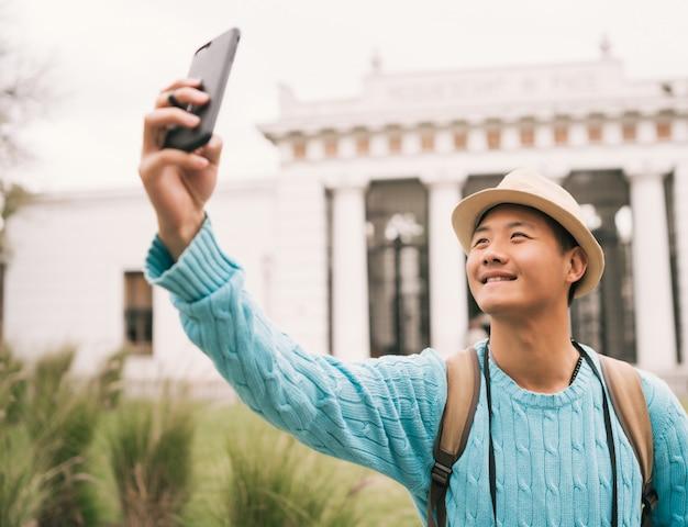 Asiatischer tourist, der ein selfie mit handy nimmt