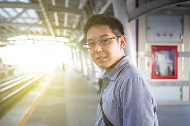 Asiatischer tourist, der oben auf einen stadtzug am bahnhofsabschluß wartet. bahnsteig ohne menschen.
