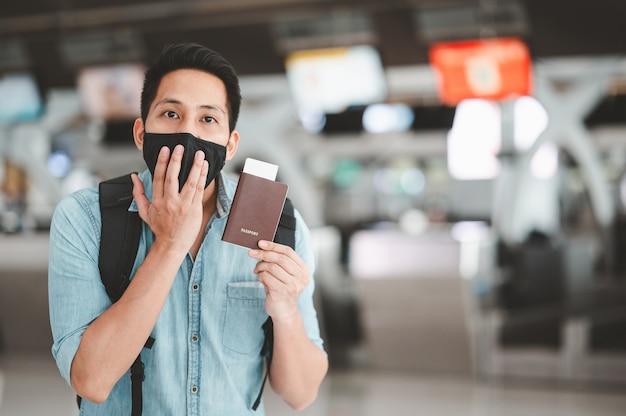 Asiatischer tourist, der proaktive gesichtsmaske trägt, die aufgeregt und überrascht fühlt
