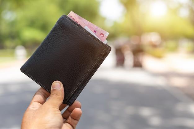 Asiatischer tourist, der seine schwarze geldbörse von anderen leuten aufhebt, die sie in der touristenattraktion fanden