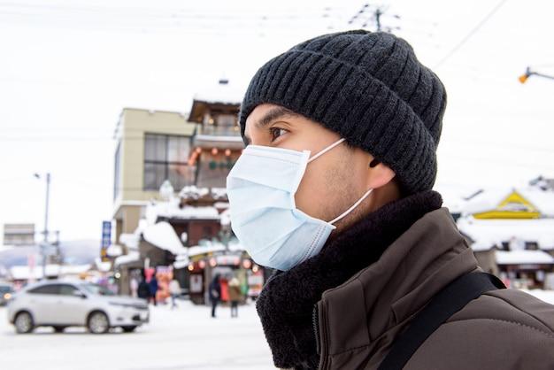 Asiatischer touristenmann, der maske trägt, die coronavirus schützt, während im freien im winter in hokkaido japan geht