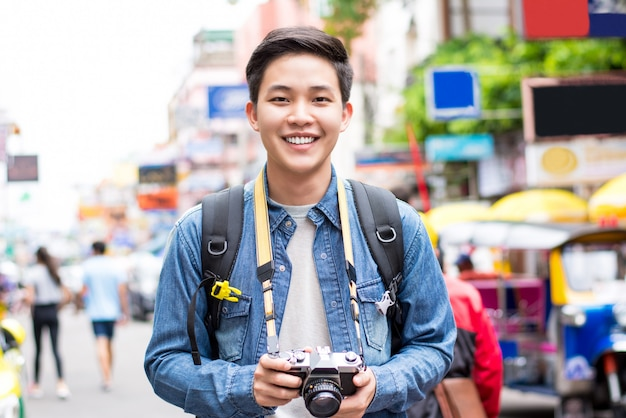 Asiatischer touristischer fotograf, der in bangkok, thailand an den feiertagen wandert