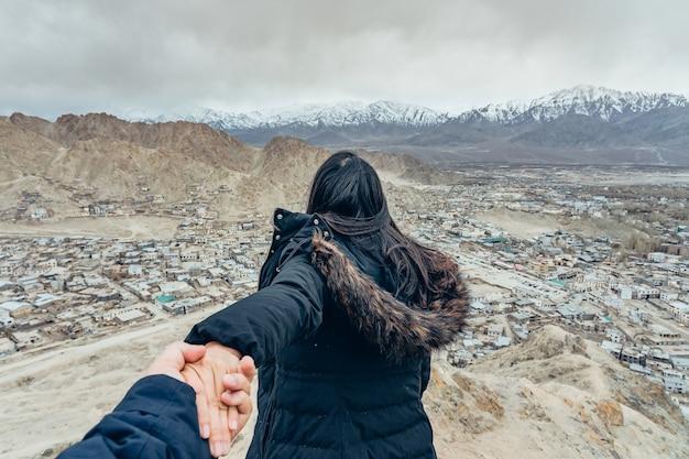 Asiatischer touristischer führender mann der jungen frau in die ansicht von leh ladakh-stadt in leh, ladakh, indien.