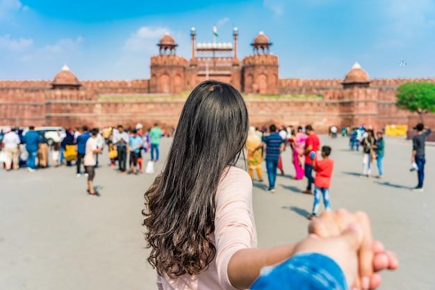 Asiatischer touristischer führender mann der jungen frau in rotes fort (lal qila) delhi mit indischer flagge in altem delhi, indien.