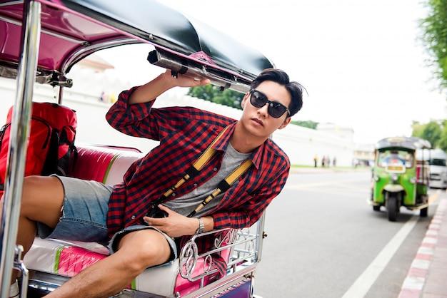 Asiatischer touristischer mann, der tuktuk-taxi beim reisen in bangkok thailand reitet