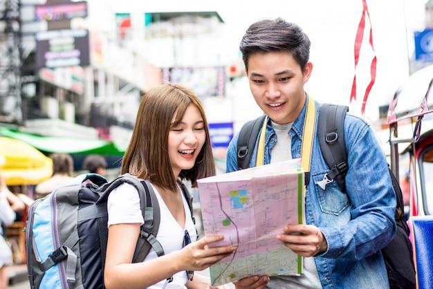 Asiatischer touristischer wanderer der jungen paare, der nach richtung auf die karte sucht