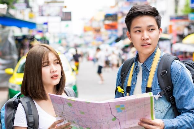 Asiatischer touristischer wanderer der jungen paare, der verloren erhält und nach richtung sucht