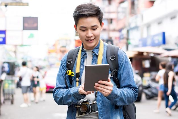 Asiatischer touristischer wanderer, der tablette beim reisen in straße thailand khao san verwendet