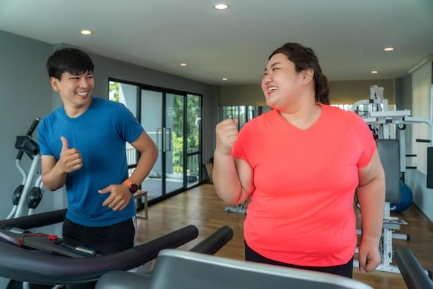 Asiatischer trainermann und überladene frau, die training auf tretmühle in der turnhalle ausübt
