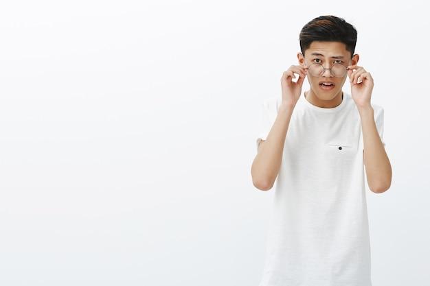 Asiatischer typ, der die brille abnimmt, als zweifelhaft, seltsame dinge zu sehen, die erstaunt und überrascht den offenen mund vor interesse sehen